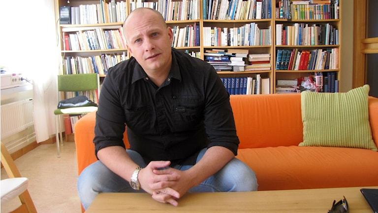 Nicklas Platow (M) sitter framför bokhyll. Foto: Jerker Hagman/Sveriges Radio.