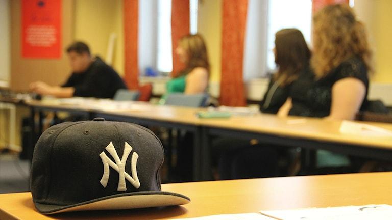 En svart keps ligger på en skolbänk. I bakgrunden syns fyra elever som tittar åt vänster. Foto: Frank Luthardt/Sveriges Radio.