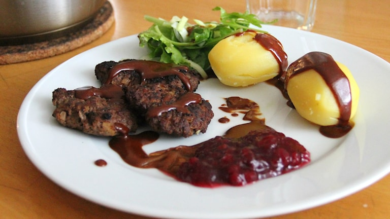 En tallrik med tre köttfärsbiffar, två potatis, lingonsylt och sallad på. Ovanpå maten har det ringlats brun gräddsås. Foto: Frank Luthardt/Sveriges Radio.