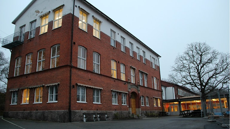 Snäckebacksskolans gamla byggnad och en del av skolgården en gråmulen höstsdag.