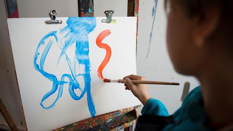Ett barn som syns från sidan när han målar.