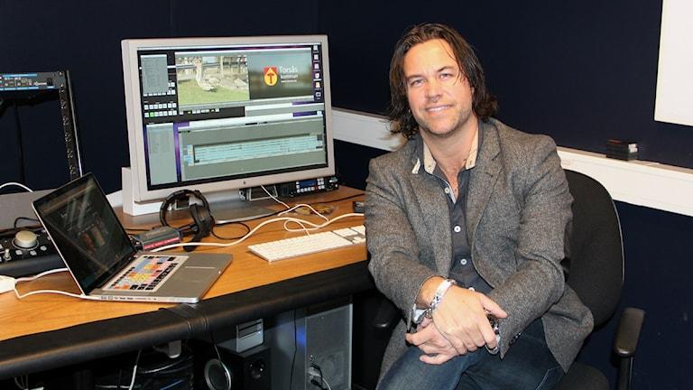 Maxe Axelsson sitter framför en stor datorskärm och en bärbar dator i Vision4yous filmljudstudio i Torsås. Foto: Frank Luthardt/Sveriges Radio.