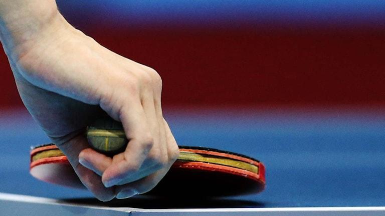 En hand och ett bordtennisrack på ett bord i närbild. Foto: Sergei Grits/Scanpix.
