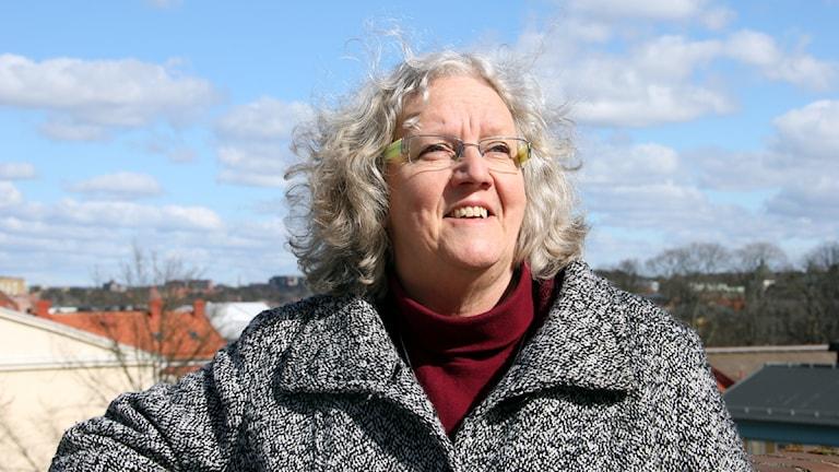 Inga-Lena Fischer lutar sig mot en mur och tittar upp mot en blå himmel.  Foto: Stina Linde/Sveriges Radio.