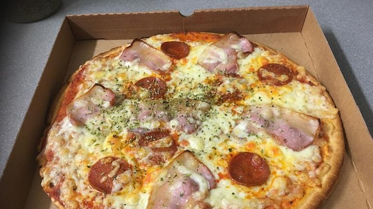 En pizza med ost, tomat och bacon.