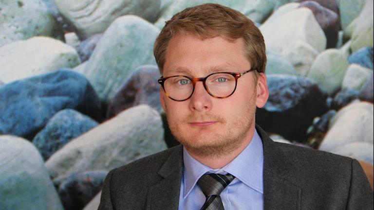 Närbild på en man i blå skjorta och grå kavaj. Foto: Rebecka Gyllin/Sveriges Radio.