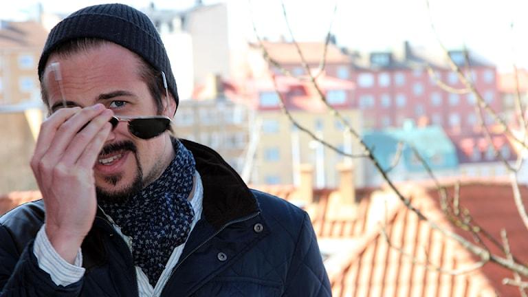 Adam Grahn, från bandet Royal Republic, tar av sig ett par solglasögon. Foto: Stina Linde/Sveriges Radio.