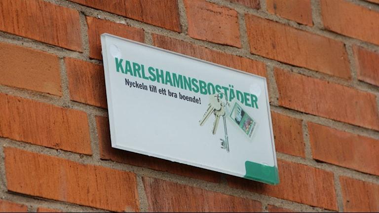 """Närbild på en skylt där det står """"Karlshamnsbostäder"""". I bakgrunden syns rött tegel. Foto: Rebecka Gyllin/Sveriges Radio."""