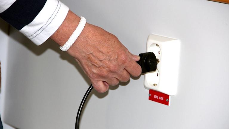 En hand som sätter i en kontakt i ett uttag i väggen. Foto: Tove Kluge.