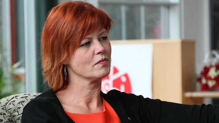 Närbild på en kvinna med rött, röd top och svart tröja. Foto: Rebecka Gyllin/Sveriges Radio.