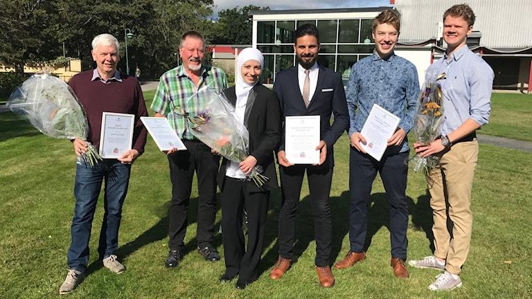 Sex personer står bredvid varandra, de ha alla vunnit ett pris och har därför blommor och varsin tavla i händerna.