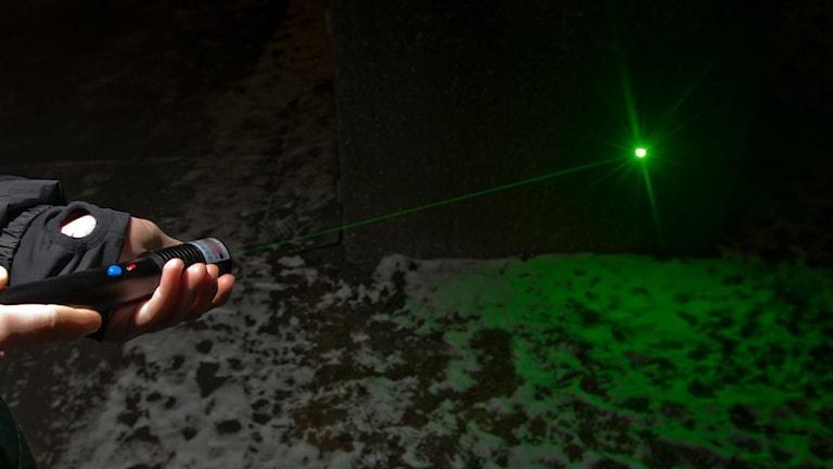 En person håller i en laserpekare som avger en grön punkt på väggen. Foto: Scanpix.