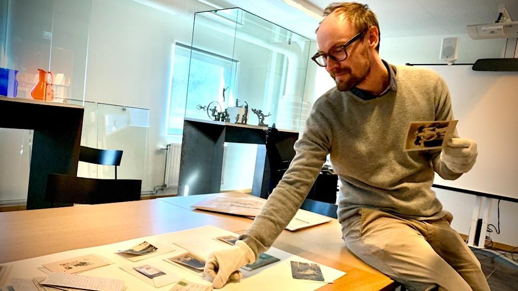 Christoffer Sandahl från Blekinge museum visar upp gamla vykort.