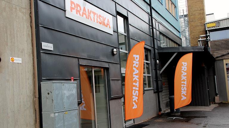 Praktiska Gymnasiets fasad, med två orange flaggor utanför. Foto: Stina Linde/Sveriges Radio.