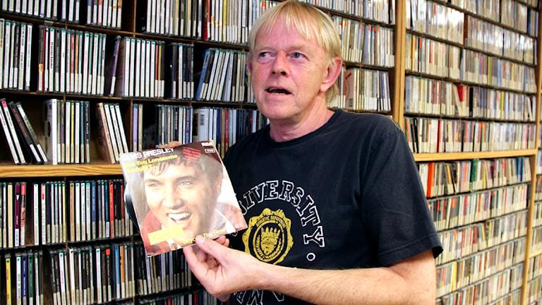 """Musikredaktören Alf Carlsson står framför en bokhylla full av skivor med Elvis """"Are you lonesome tonight"""" i handen. Foto: Stina Linde/Sveriges Radio."""