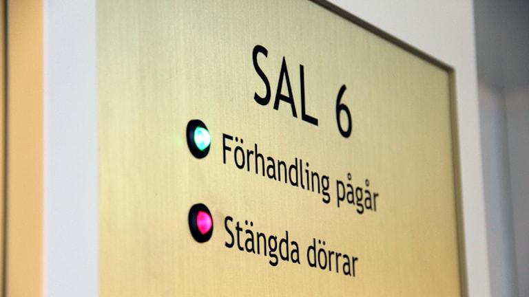 En skylt där det dtår att häktningsförhandling pågår och att det görs bakom stängda dörrar. Foto: Rebecka Gyllin/Sveriges Radio.