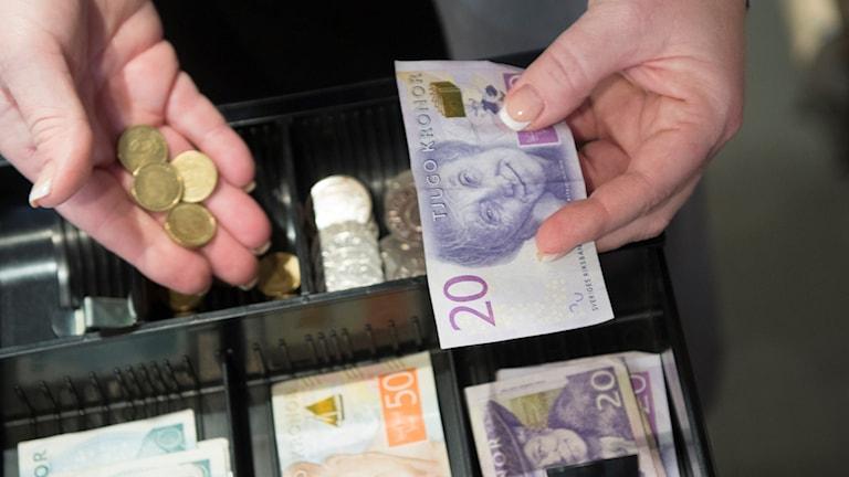 Pengar i en kassaapparat.