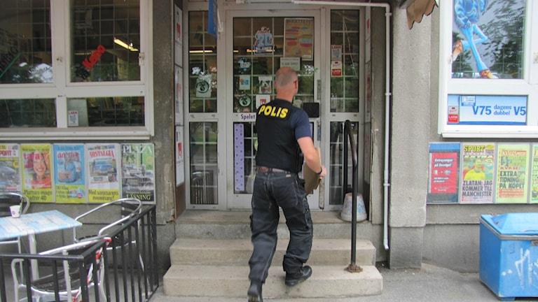 En polisman är på väg in i tobaksaffären
