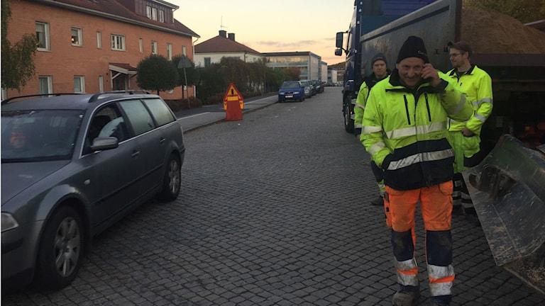 Vägarbetare i Ronneby när en bil passerar.