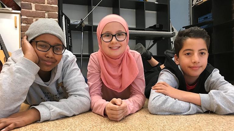Närbild på tre barn som ligger bredvid varandra.
