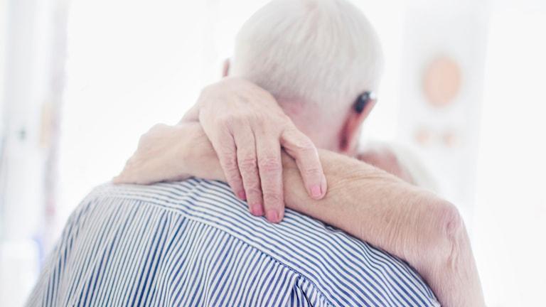 Ett äldre par håller varandra om halsen.