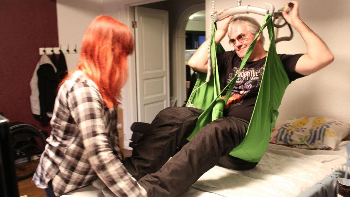 En förlamad man hänger i en taklift, han håller på att lyftas ur sängen. Foto: Rebecka Gyllin/Sveriges Radio.