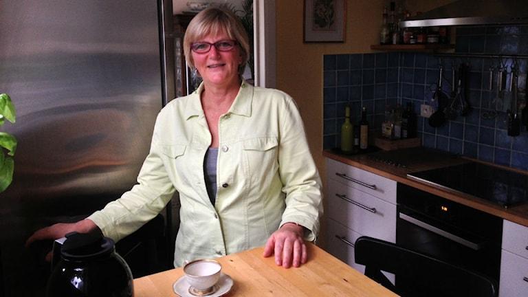 En kvinna står vid köksbordet i sitt kök. Foto: Rebecka Gyllin/Sveriges Radio.