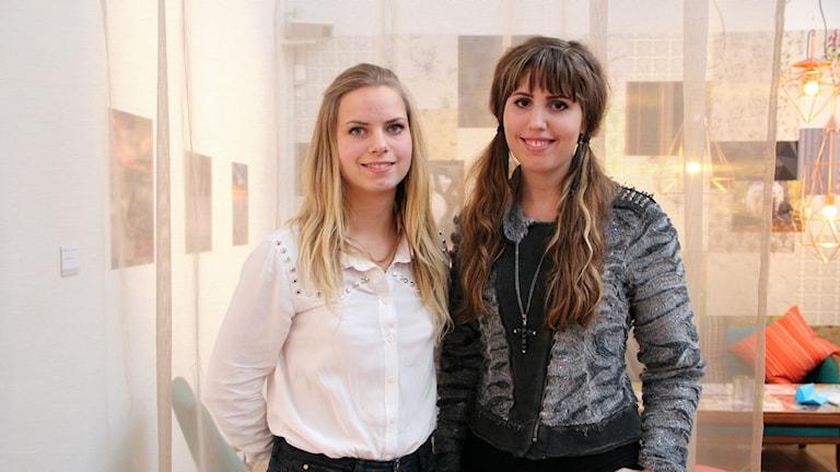 Sissa Pagels och Louise Lindén står bredvid varandra framför ett tunt genomskinligt skynke. På väggen i bakgrunden hänger mång tavlor.