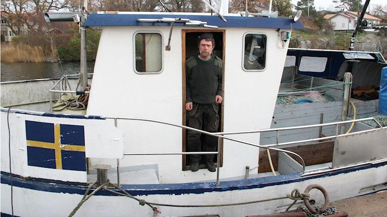 En man står på sin fiskebåt och tittar mot kameran. Foto: Rebecka Gyllin/Sveriges Radio.