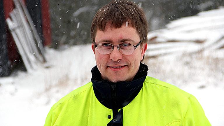 Jonny Arvidsson står på sin snötäckta gårdsplan i en neongul jacka.