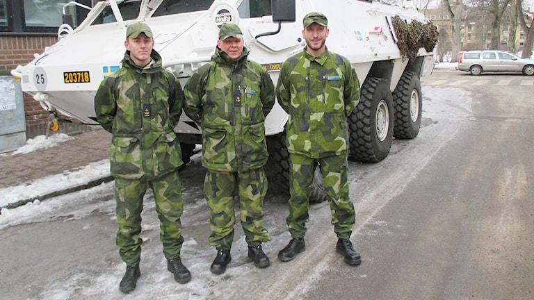 Tre militärer står framför en parkerad pansarterrängbil.
