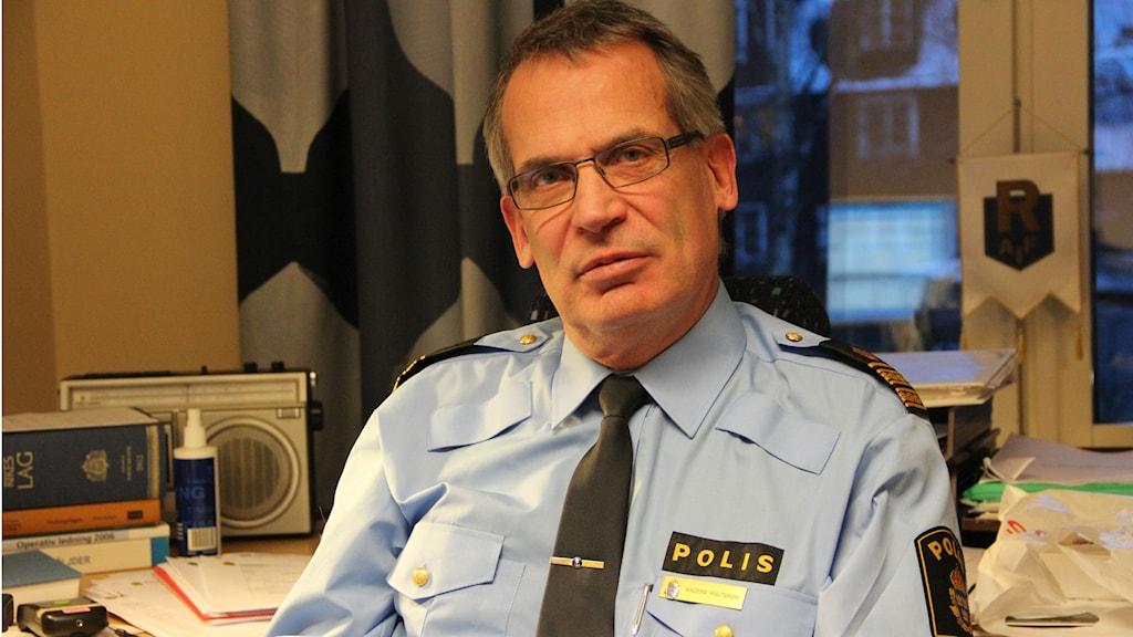 En man i polisuniform sitter på ett kontor. Foto: Rebecka Gyllin/Sveriges Radio.