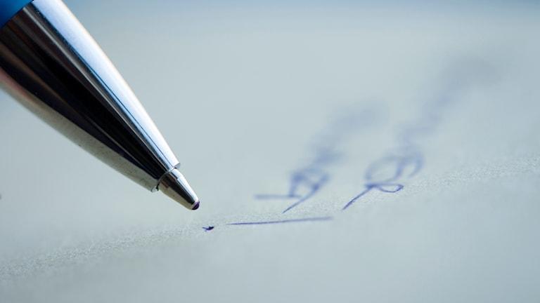Närbild på när någon skriver på ett papper.