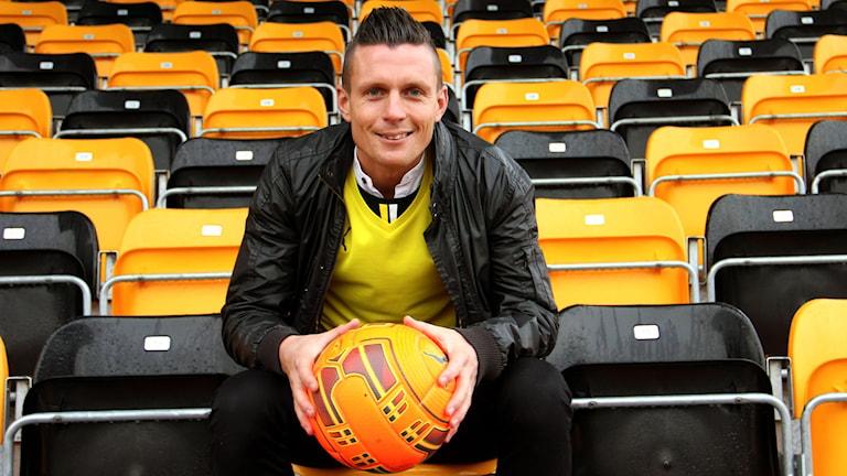 Maifspelaren Kristian haynes sitter på ett tomt Strandvallen med en orange fotboll i famnen. Foto: Stina Linde/Sveriges Radio.