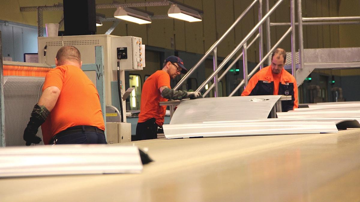Volvoanställda i orange tröjor står vid ett löpande band och behandlar bildörrar. Foto: Stina Linde/Sveriges Radio