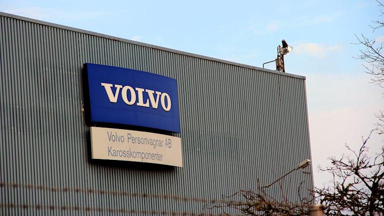 En blå Volvoskylt på en grå vägg. Foto: Stina Linde/Sveriges Radio