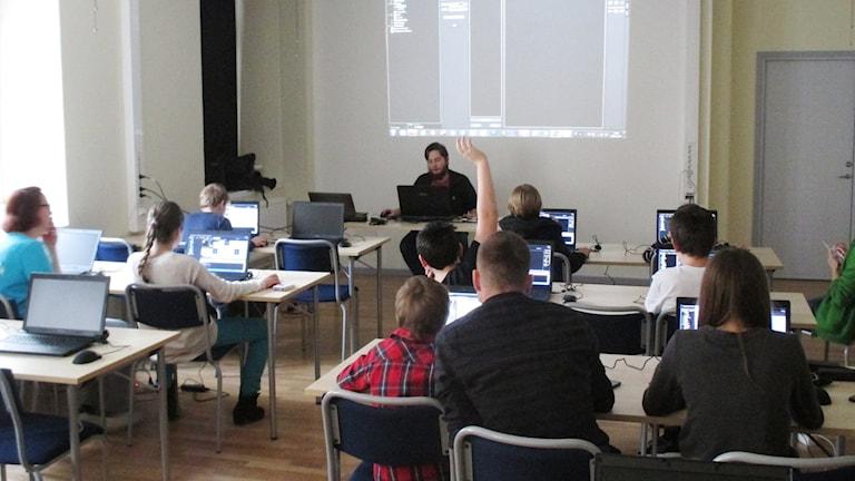 Elever sitter i ett klassrum med lärare längst fram.