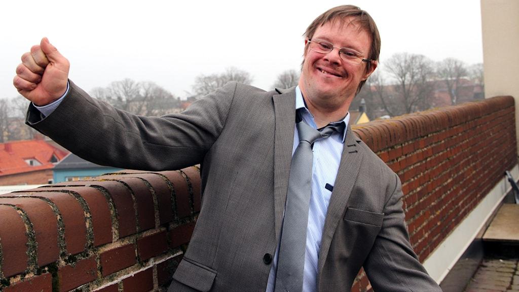 Bloggaren Henrik Daleke står med händerna i luften vid en stenmur. Foto: Stina Linde/Sveriges Radio