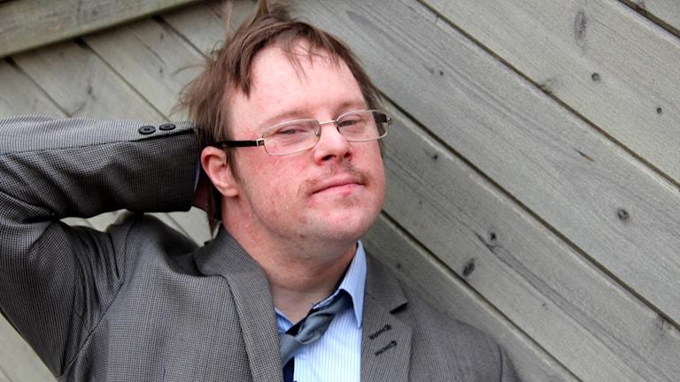 Bloggaren Henrik Daleke står och lutar sig mot ett träplank, samtidigt som han stryker sig över håret. Foto: Stina Linde/Sveriges Radio