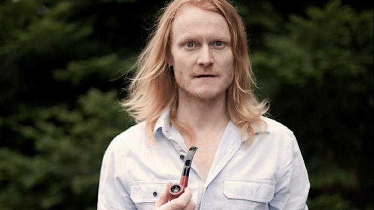 Lats Lindquist står med en pipa i handen. Foto: FRANZ FELDMANIS