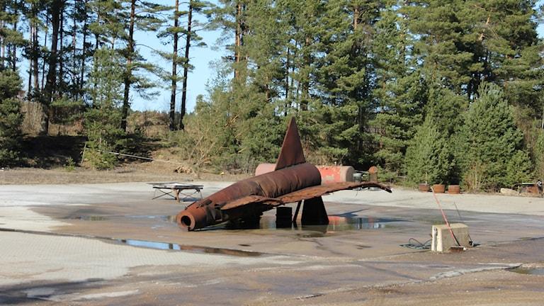 En rotsröd kopia av ett stridsflygplan på brandövningsplatsen på F17 i Kallinge. Foto: Mikael Eriksson/Sveriges Radio