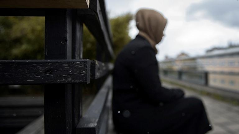 Kvinna sitter på bänk