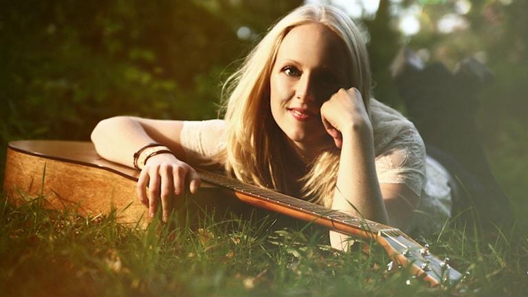 Marie Nilsson ligger i grönt gräs med armen om en gitarr. Foto: Amanda Stiverius