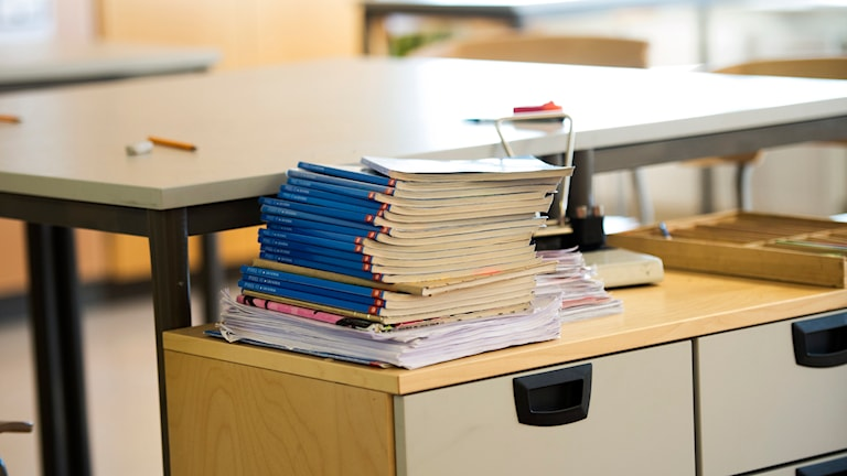 En trave skolböcker ligger på en bänk. Foto: