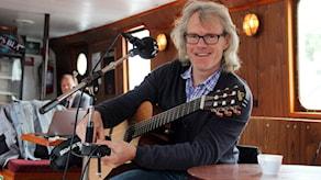 Trubaduren Jens U Nilsson med sin gitarr.