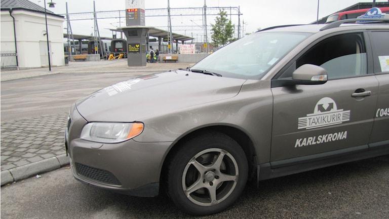 En grå taxibil står vid en tågstation. Foto: Rebecka Gyllin/Sveriges Radio