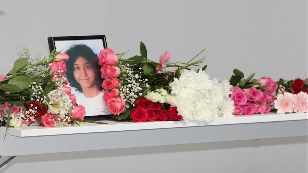 Ett fotografi på en liten tjej är omringat av massa blommor. Foto: Andrea Jilder/Sveriges Radio