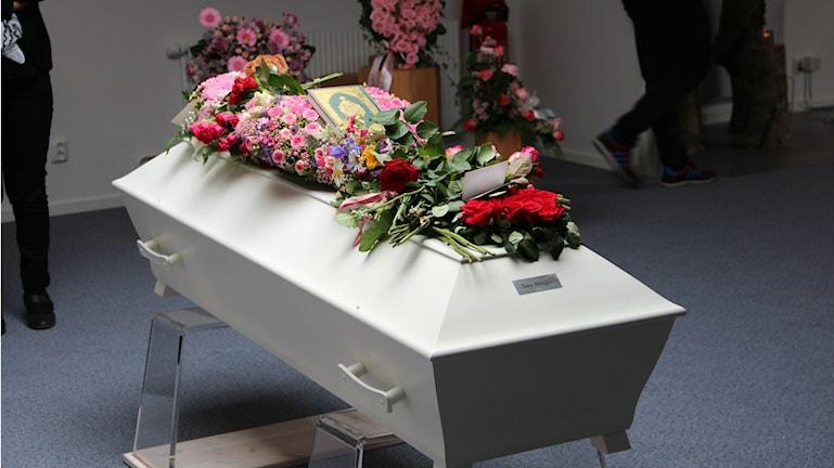 En liten vit kista med blommor ovanpå. Foto: Andrea Jilder/Sveriges Radio
