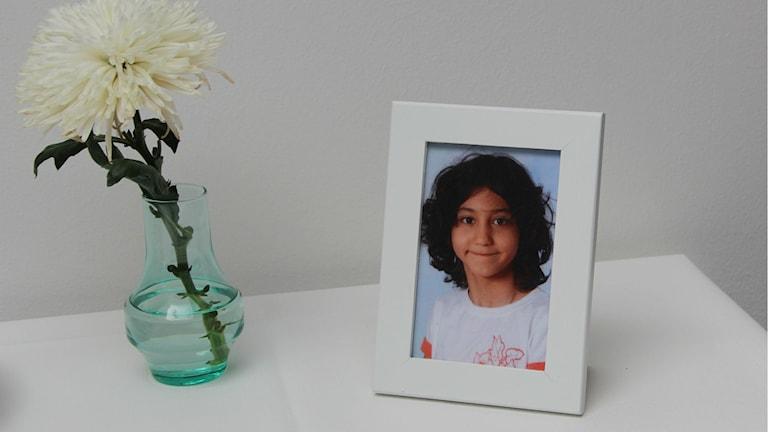 Närbild på ett fotografi, vid sidan om står en blomma. Foto: Andrea Jilder/Sveriges Radio