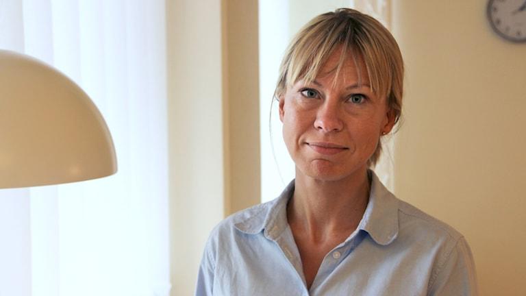 Kommunalrådet Sara Rudolfsson står vid ett fönster i blå blus och tittar in i kameran.